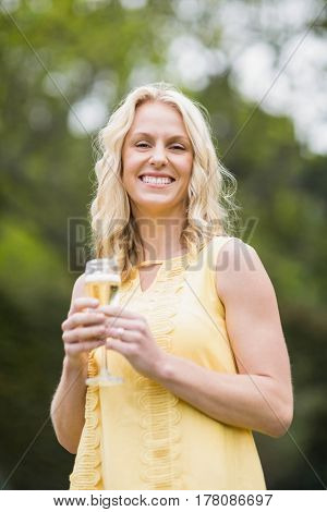 Happy woman drinking glass of champagne outside