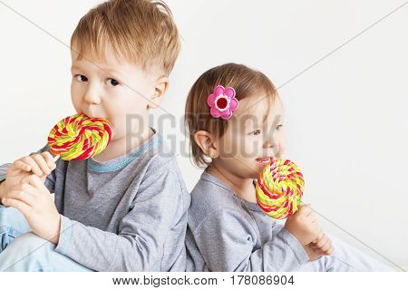 Small kids eating lollipops. Happy children with a big delicious candy. Portrait of a happy siblings - boy and girl. Little Brother and sister against a white background