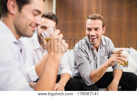 Group of men having cocktail drinks at party