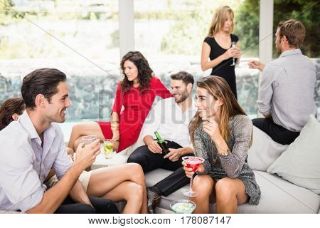Group of friends talking to each other and having cocktail drinks at party