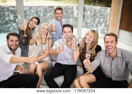 Portrait of friends smiling and holding glasses of champagne at party