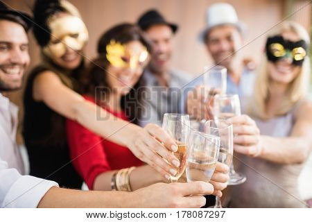 Friends with masks on holding champagne glasses at the party