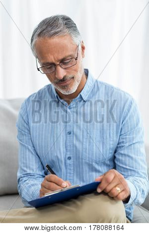 Doctor writing on a clipboard at home