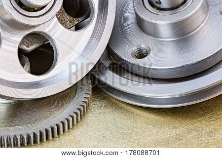 Industrial Metal Pulleys And Cogwheel On Scratched Brass Background
