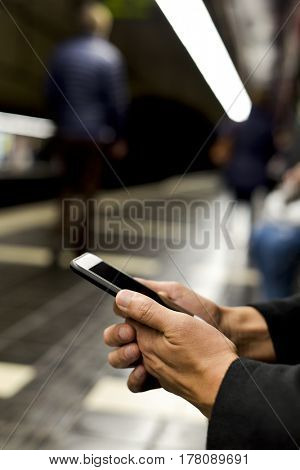 closeup of a young caucasian man using a smartphone in an underground train or tram station