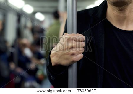 closeup of a young caucasian man traveling as a passenger in a train car, standing and grabbing a vertical bar with his right hand