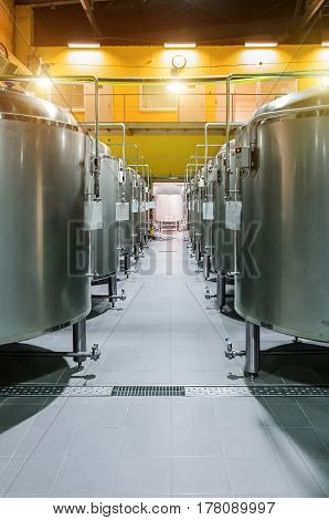 Modern Beer Factory. Rows of steel tanks for the storage and fermentation of beer. Sunlight effect