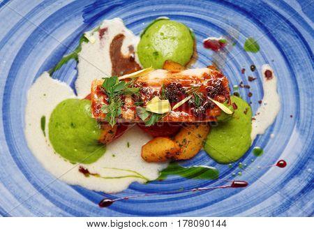 Chicken fillet on blue porcelain plate, unusual food design
