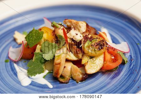 Chicken salad with vegetables, mint and cilantro on blue plate