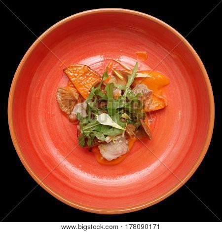 Game bird fillet with sweet potato mash and mushrooms in red clay plate, isolated on black background