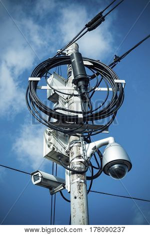 Busy electricity line and security camera against blue sky. Stock image.