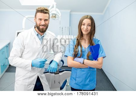 Portrait of handsome dentist with young female assistant in uniform at the dental office