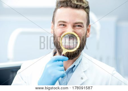 Portrait of handsome dentist holding magnifying glass in front of his toothy smile at the dental office