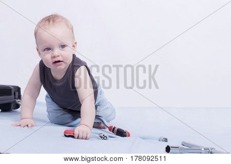 Cute toddler on the grey background playing with wrench. Horizontal studio shot. Copy space