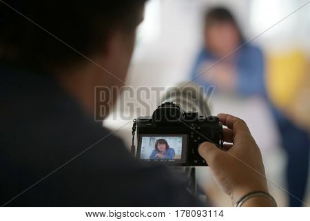 Photographer behind camera taking picture of model