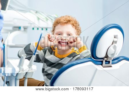 Portrait of a happy young boy with a toothy smile sitting on the dental chair at the dental office
