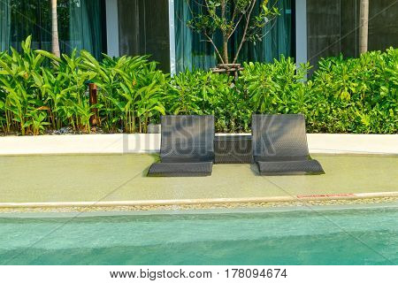 Beach chairs in luxury swimming pool at tropical hotel resort relaxing and leisure time in the pool.
