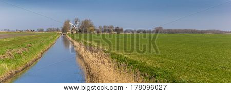 Panorama of a river leading to a windmill in Groningen Holland