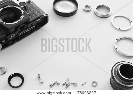 Details of the old manual lens in the frame, free space. Laid lens disassembled in a circle on a white background. Technical background. Service center.
