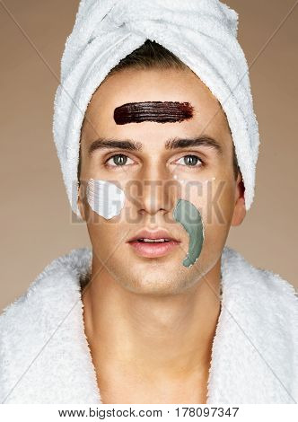 Handsome man with three different face masks (chocolate cream and clay masks). Photo of man with perfect skin. Grooming himself