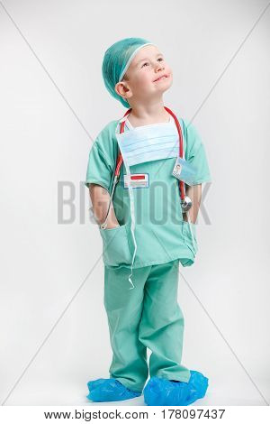 Full length portrait of cute smiling boy playing a doctor. Different occupations.