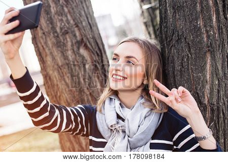 Young pretty woman is posing while photographing herself on mobile phone for social network picture during recreation time in parkcharming blonde female is making self portrait with phone camera