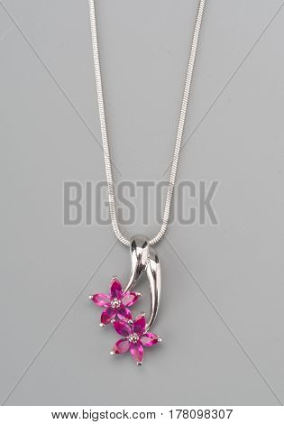 Silver pendant with rose gem shot on gray background