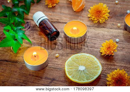 Citrus and herbs aroma oil concept. Essential glass bottle, burning yellow aroma candles, orange daisy flowers, lemon slice and ivy branch with green leaves on a wooden background