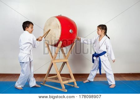 Two children in a kimono pounding the drum. Fighting position active lifestyle practicing fighting techniques