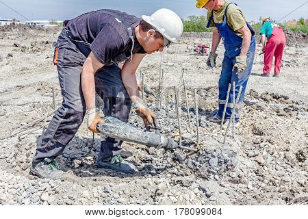 Zrenjanin Vojvodina Serbia - April 30 2015: Constructions workers are using jackhammer to realign reinforced pillars in the ground.