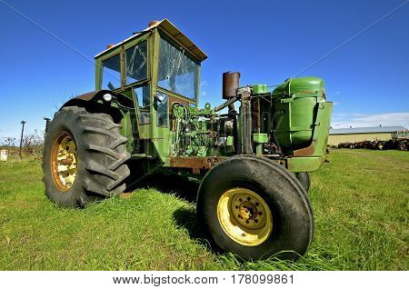 A tractor with a cab missing an engine is left for parts, salvage and scrap iron.