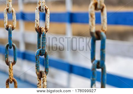 Rusty metal chain on a white and blue fence.