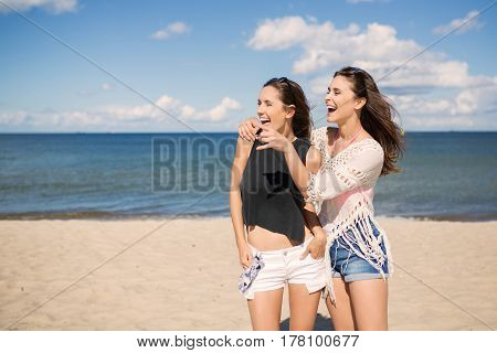 Two Pretty Girls On Beach Looking At Something Laughing