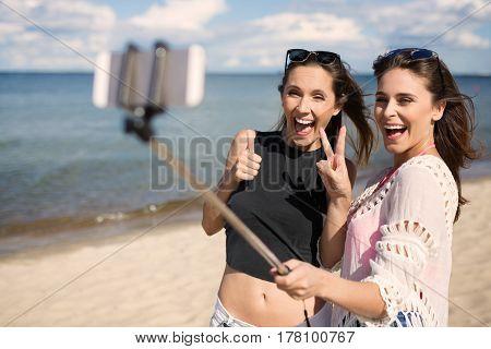 Two Happy Female Friends Taking Selfie On Beach