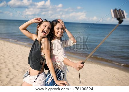 Two Happy Women Taking Selfie On Beach Fooling Around