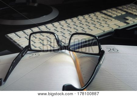 Glasses in a black casing on the daily log against the background of the computer keypad in the small depth of sharpness.Low contrast. Darkly at the edges.Vintage. Horizontal format. Indoors. Color. Photo.