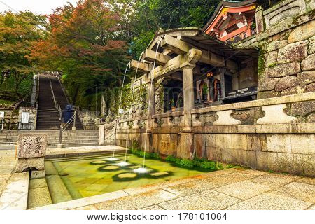 KYOTO, JAPAN - NOVEMBER 10, 2016: Three streams of Otowa waterfall at Kiyomizu-dera temple in Kyoto, Japan. Visitors believe that water can enhance health, longevity, and success in studies.