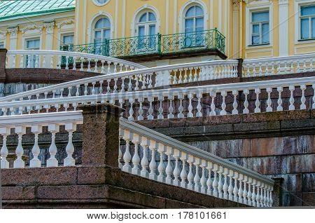 Geometric lines with white balustrades and railings decorative marble stairs in the background of the balcony and the main facade of the Palace in Oranienbaum.