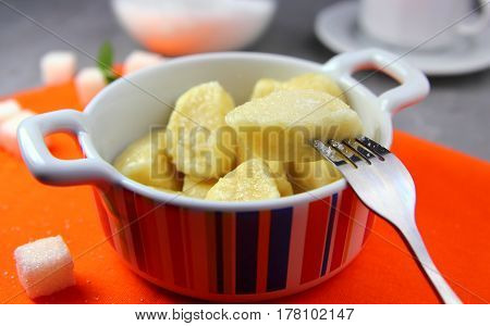 cottage cheese lazy dumplings with sugar in large ceramic white bowl