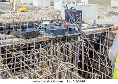 Industrial shot of construction worker who is welding metal frame cage of armature inside of demountable wooden mold for concreting pillar base.