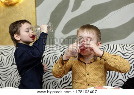 Two children drinking juice in a cafe