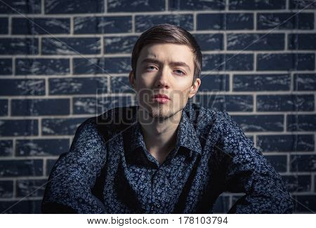 Portrait of confident handsome young man in shirt with long sleeves