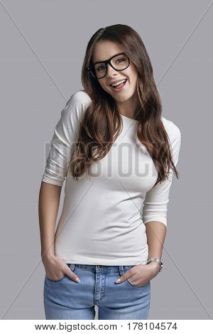 Hey! Playful young woman in casual wear keeping hands in pockets and looking at camera while standing against grey background