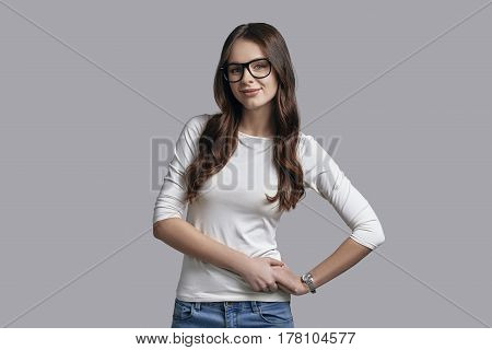 Confident and beautiful. Attractive young woman in casual wear keeping hands on hip and looking at camera while standing against grey background