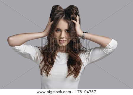 Loving her hair. Attractive young woman in casual wear playing with her hair and looking at camera while standing against grey background
