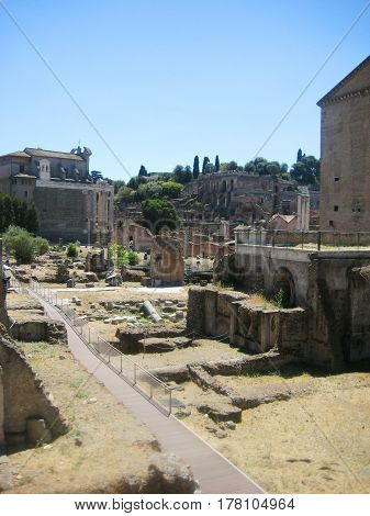 Roman Forum historical plaza with ruins of ancient government buildings and modern travel path for tourists in Rome city center in Italy. Famous roman tourist attraction with blue sky background
