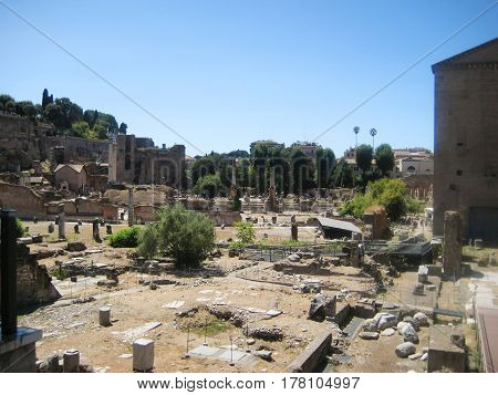 Roman Forum ancient historical plaza with ruins of old government buildings in Rome city center in Italy. Famous roman tourist attraction with blue sky empty background