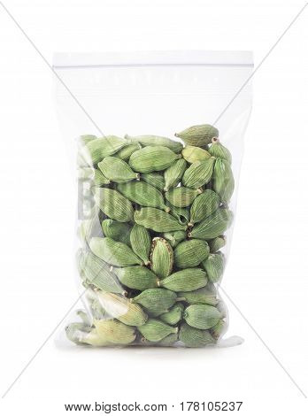 green cardamom seeds in plastic zipper bag isolated on white background. Cardamom pods in bag. Indian spice. Condiment