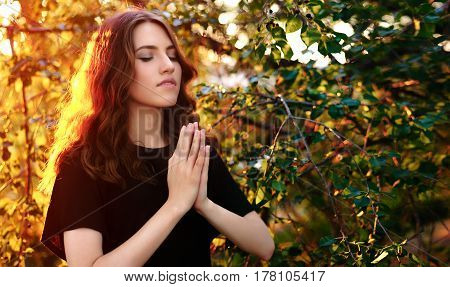 The girl prays in nature. eyes closed.
