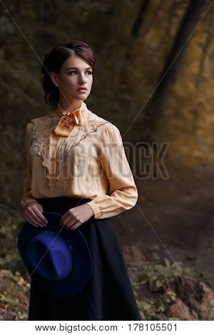 outdoor fashion portrait of sensual stylish girl in vintage blouse with bow. Young woman with romantic hairstyle and floppy hat walks in the forest. Beautiful brunette girl. Female retro look